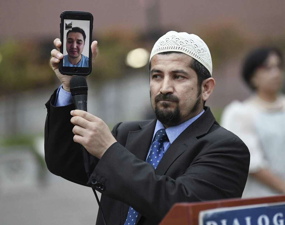 """Imam Beytula Colak holds a phone as a man who prefers to be identified only as """"Serdar D,"""" who is a survivor of the mosque shootings in New Zealand, speaks during a gathering in Main Plaza on Saturday, March 23, 2019, for a vigil for the victims of the mosque attacks in New Zealand a week ago. The event was put on by the Muslim Children Education and Civic Center & Turkish Raindrop House."""