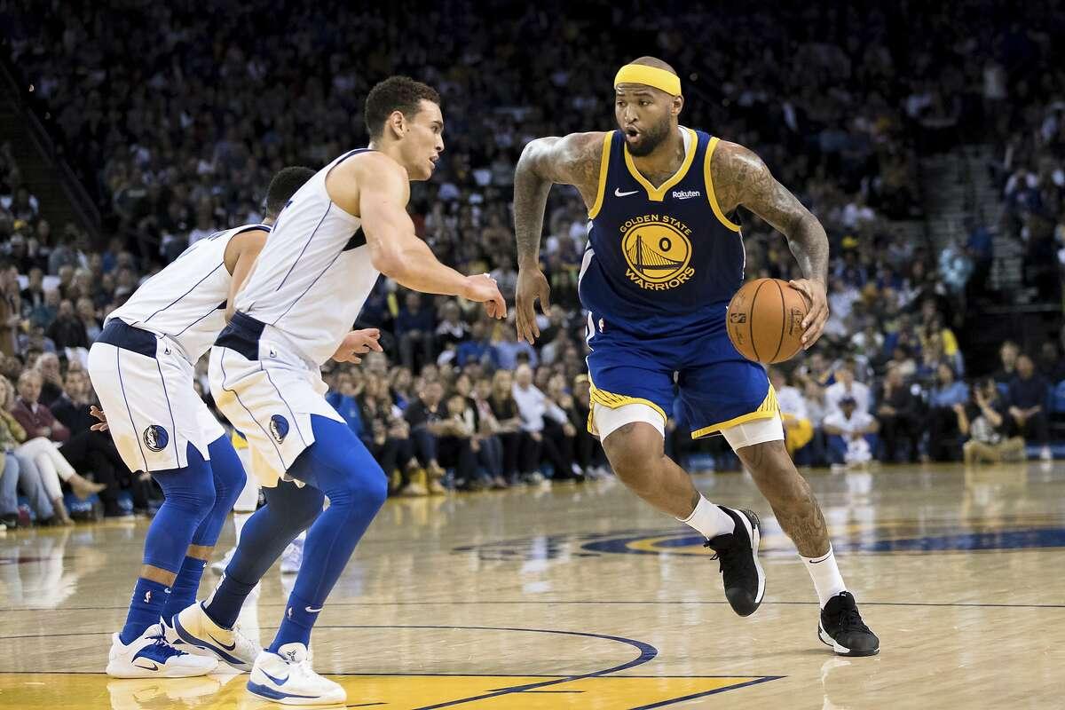 Golden State Warriors center DeMarcus Cousins (0) dibbles as Dallas Mavericks forward Dwight Powell, left, in the second half of an NBA basketball game Saturday, March 23, 2019 in Oakland, Calif. The Mavericks won 126-91. (AP Photo/John Hefti)