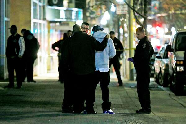 A man is comforted as police investigate a shooting along Fillmore Street on Saturday, March 23, 2019, in San Francisco, Calif. Police said that one person is dead and another three injured in the shooting.