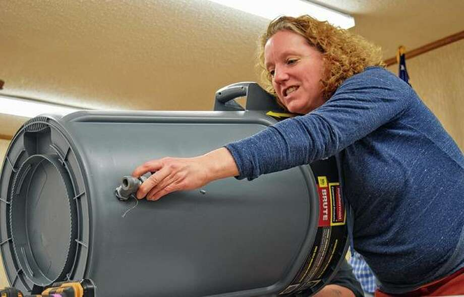 Michelle Berg Vogel, a program coordinator for the University of Illionis Extension, demonstrates how to connect a spigot to a trash can in order to create a rain barrel Saturday at the University of Illinois Extension office during Gardener's Day. Photo: Samantha McDaniel-Ogletree | Journal-Courier