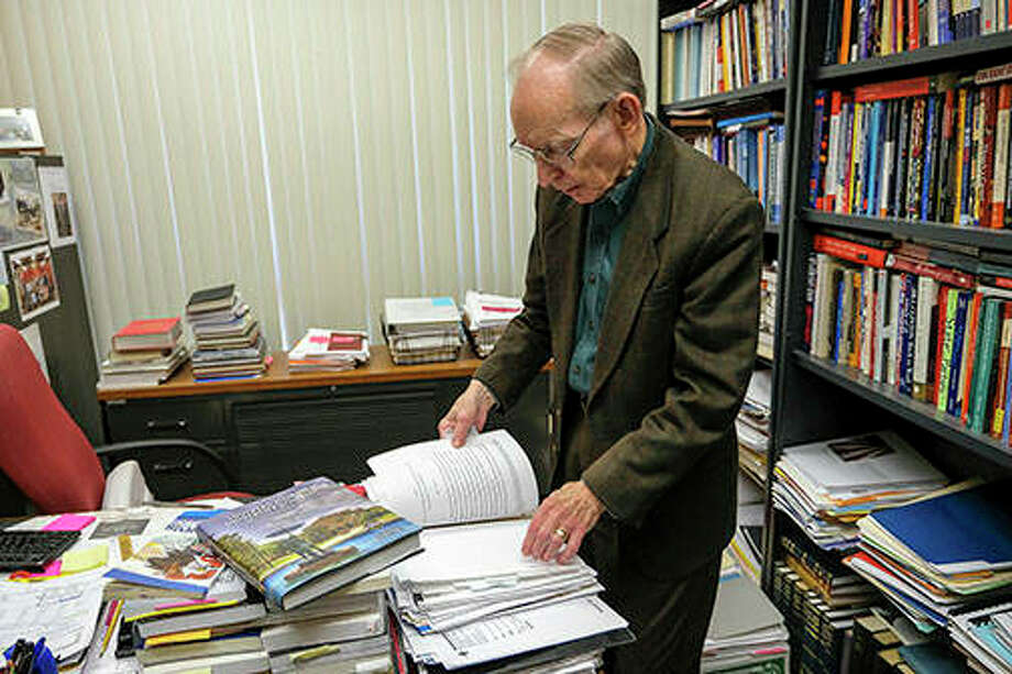 """John Jackson, a professor at SIU for 50 years, leafs through the various manuscripts from contributors that he edited and compiled into """"Southern Illinois University at 150 Years,"""" a book commemorating the university's 150th anniversary this year. Photo: Byron Hetzler 