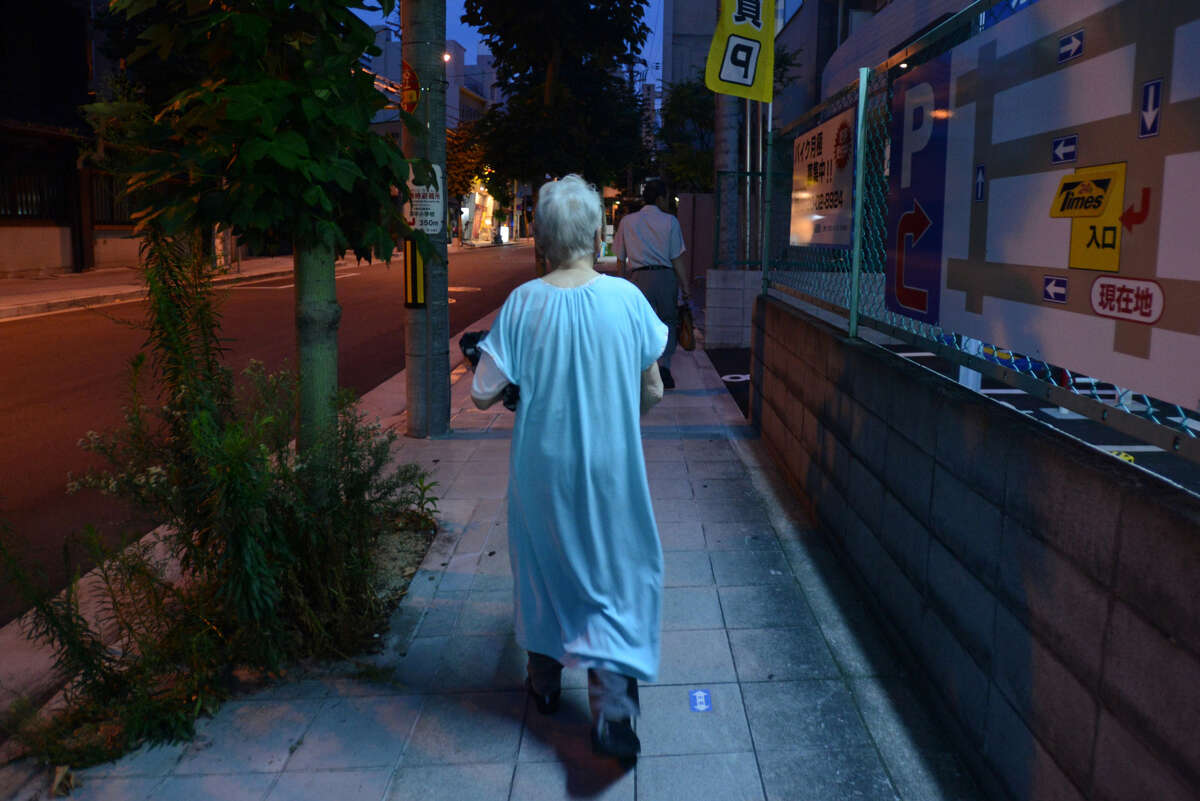 A woman who was diagnosed with Alzheimer's disease walks near her apartment in Osaka, Japan, on Aug. 6, 2014.