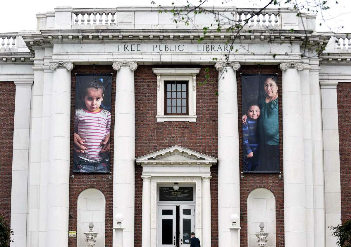 Photographs of immigrants hang in the front of the New Haven Free Public Library in New Haven on June 13, 2018.