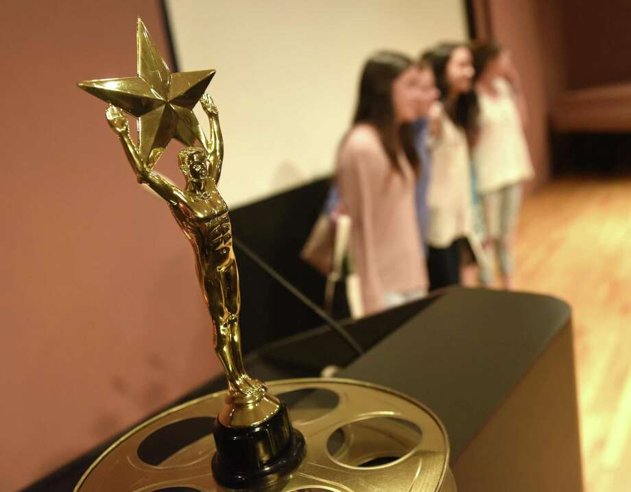 Young filmmakers pose for a photo by the best film award at the fifth annual Greenwich Youth Film Festival at Greenwich Library's Cole Auditorium in Greenwich, Conn. Sunday, April 24, 2016. The eighth annual Greenwich Youth Film Festival will start at 6:30 p.m. Monday in Greenwich Library's Cole Auditorium. Photo: Tyler Sizemore / Hearst Connecticut Media / Greenwich Time