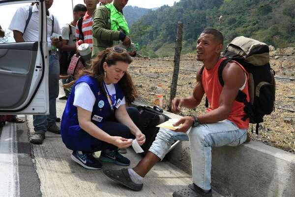 Cristal Montañéz applies a numbing bandage to a years-old leg wound on Junior Ríos Olivares, a Venezuelan who plans to hike 1,000 miles to Ecuador.