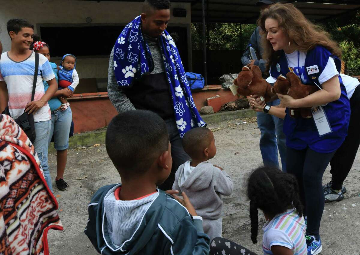 Cristal Montañéz hands out her signature teddy bears to Venezuelan children outside a migrant shelter on a Colombian highway.