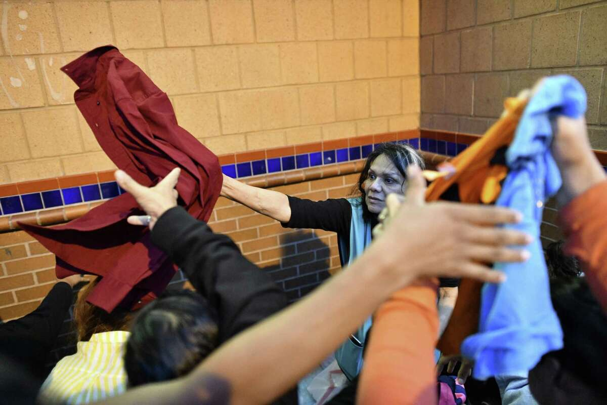 Elena Arredondo, a volunteer with Catholic Charities in Laredo, passes out donated clothing to Honduran migrants outside the bus station in Laredo this month.