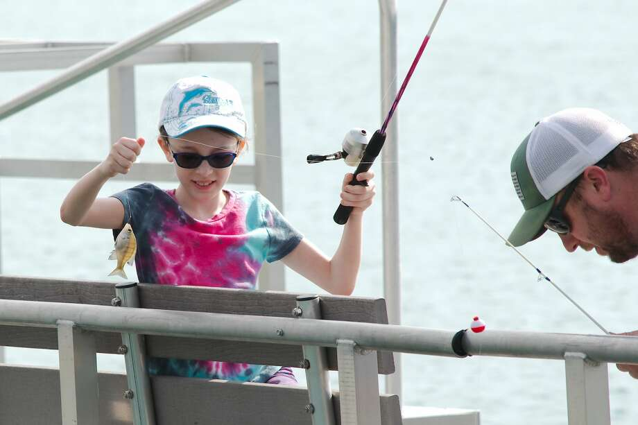 Payton Oliver pulls in a sunfish while fishing with her father Eric Oliver at Lake Friendswood Sunday, Mar. 24. Photo: Kirk Sides/Staff Photographer