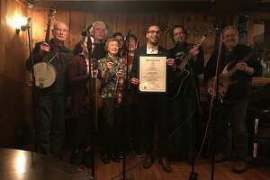"""State Rep. Raghib Allie-Brennan presents a citation from the General Assembly to the """"Fiddler's Brawl"""" in recognition of 25 consecutive years of monthly performances in Bethel."""