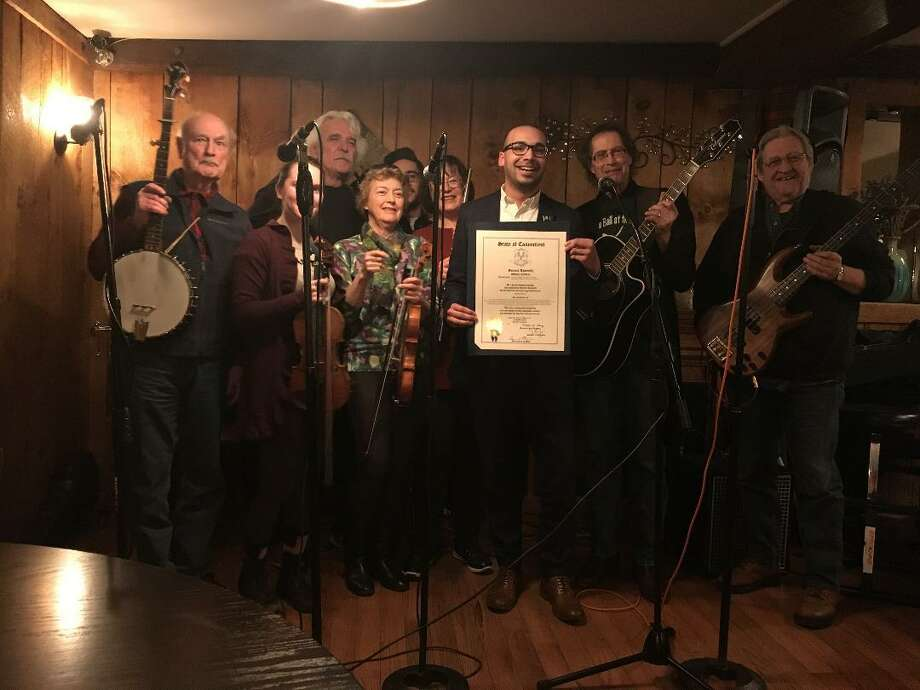 """State Rep. Raghib Allie-Brennan presents a citation from the General Assembly to the """"Fiddler's Brawl"""" in recognition of 25 consecutive years of monthly performances in Bethel. Photo: / Contributed Photo"""