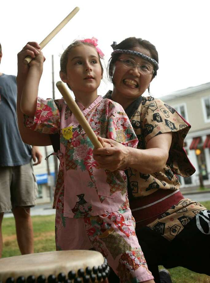Juliette Savarino, 5 of Westport, learns to play a traditional Japanese drum with the help of Masayo Kaneko of New York City at the Bon Odori Japanese Summer Festival at Jesup Green in downtown Westport on Sunday, July 25, 2010. Photo: Brian A. Pounds / Connecticut Post