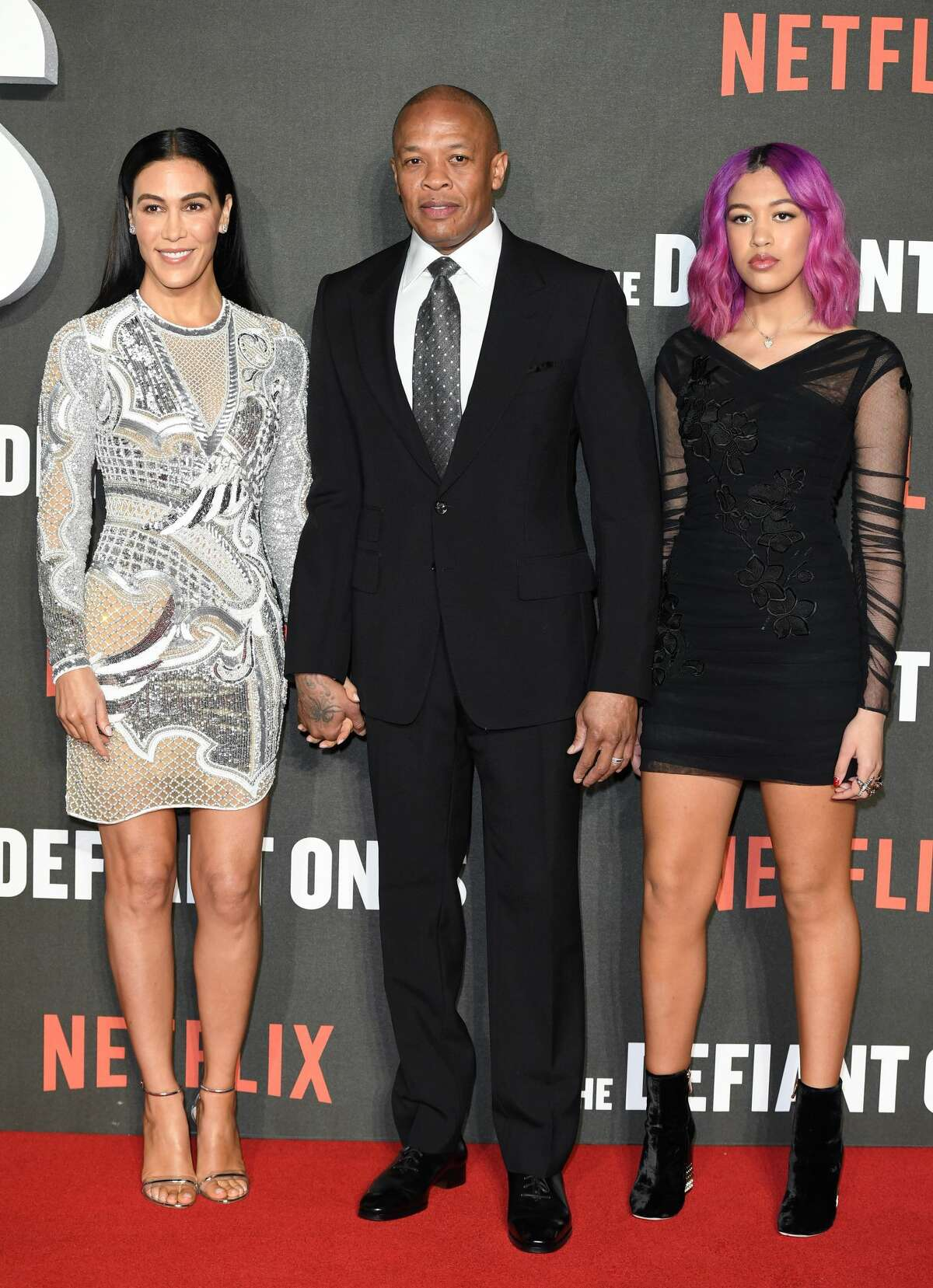 FILE - Dr. Dre, wife Nicole Young (L) and daughter Truly Young (R) attend 'The Defiant Ones' special screening at the Ritzy Picturehouse in this file photo from March 15, 2018 in London. In the aftermath of a college admission scandal involving University of Southern California, people on social media were angry that he bragged about his daughter's admission into the school, reminding him that he donated $70 million to the school along with Jimmy Iovine in 2013. Click through to learn more about the nationwide college admissions scandal. >>>