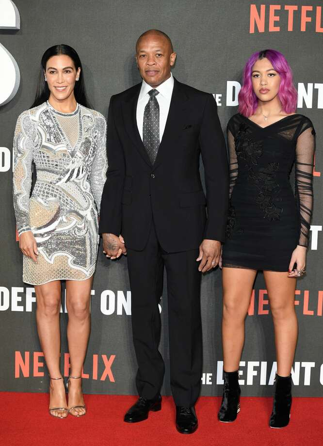 FILE – Dr. Dre, wife Nicole Young (L) and daughter Truly Young (R) attend 'The Defiant Ones' special screening at the Ritzy Picturehouse in this file photo from March 15, 2018 in London. In the aftermath of a college admission scandal involving University of Southern California, people on social media were angry that he bragged about his daughter's admission into the school, reminding him that he donated $70 million to the school along with Jimmy Iovine in 2013.