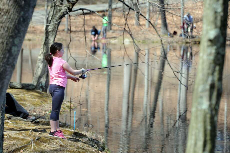 Alexa Hite, of Monroe, fishes at Great Hollow Lake, in Monroe, Conn. April 11, 2017. The Monroe Parks and Recreation Department has announced that the 2019 fishing season will open April 13 at locations throughout the state, including Great Hollow Lake. Photo: Ned Gerard / Hearst Connecticut Media / Connecticut Post