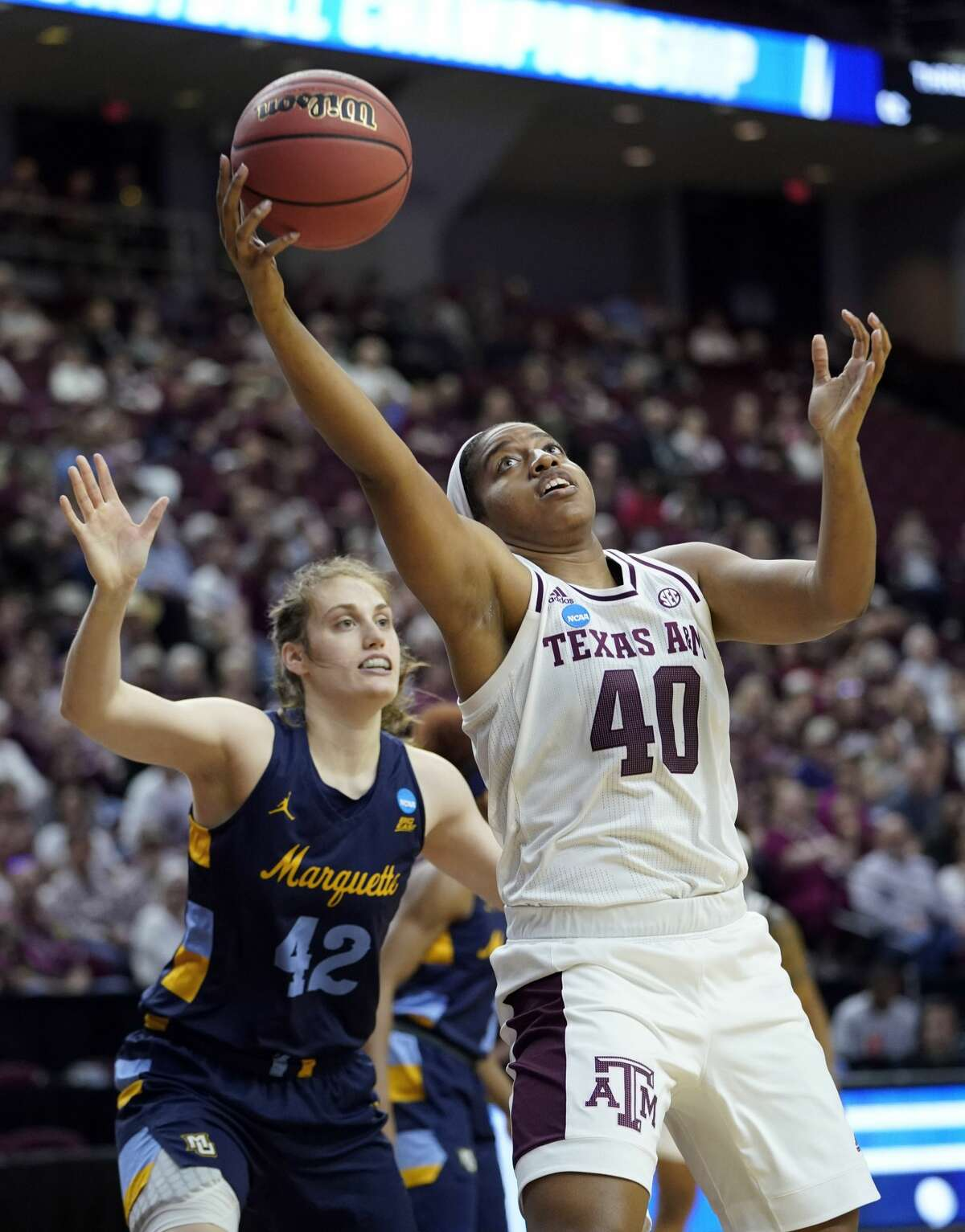 Texas A&M's Ciera Johnson (40) reaches for a pass as Marquette's Lauren Van Kleunen (42) defends during the first half of a second round women's college basketball game in the NCAA Tournament Sunday, March 24, 2019, in College Station, Texas. (AP Photo/David J. Phillip)