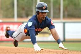 Houston Astros center fielder Tony Kemp (18) slides safely into third base during the sixth inning of a Major League Baseball spring training game against the Miami Marlins at Roger Dean Chevrolet Stadium Tuesday, Feb. 26, 2019 in Jupiter, Fla. (David Santiago/Miami Herald/TNS)