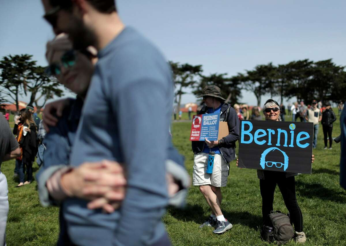 Isabella Wilk, right, and Scott Sammler, left, of Alameda hold signs in support of Democratic presidential candidate Sen. Bernie Sanders, I-Vt., before a rally at Great Meadow Park at Fort Mason in San Francisco, Calif., on Sunday, March 24, 2019.