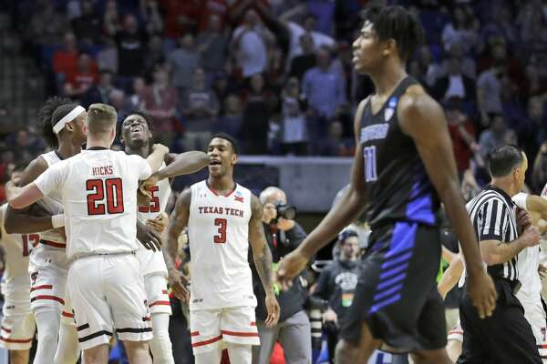Members of Texas Tech celebrate as Buffalo's Jeenathan Williams walks past in the foreground at the end of a second round men's college basketball game in the NCAA Tournament Sunday, March 24, 2019, in Tulsa, Okla. Texas Tech won 78-58. (AP Photo/Jeff Roberson)