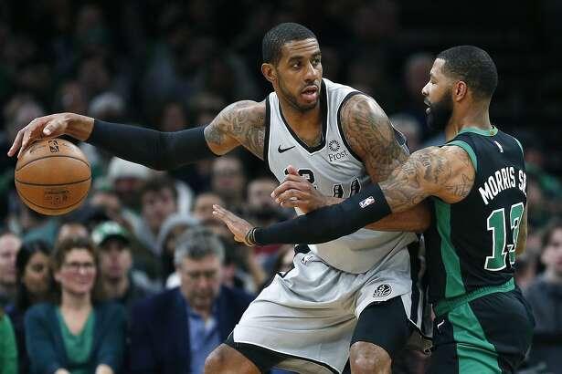 Boston Celtics' Marcus Morris (13) defends against San Antonio Spurs' LaMarcus Aldridge (12) during the first half of an NBA basketball game in Boston, Sunday, March 24, 2019 (AP Photo/Michael Dwyer)