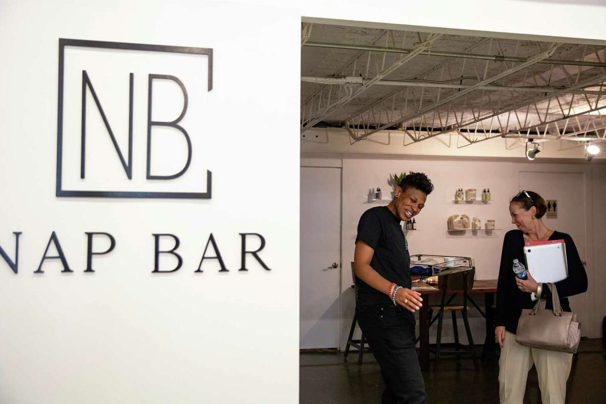 Khaliah Guillory, founder and president of Nap Bar, left, introduces her new wellness concept to Holly Smith, who popped in from next door to check out the napping facility.