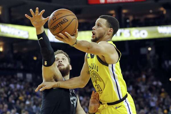 Golden State Warriors' Stephen Curry shoots around Detroit Pistons' Blake Griffin in 2nd quarter during NBA game at Oracle Arena in Oakland, Calif., on Sunday, March 24, 2019.