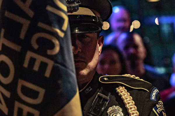 A member of the Alton Police Department Honor Guard stands at attention Friday with more than 100 police officers, firefighters and servicemen and women during the annual Mustache March 4PD event at Bluff City Bar and Grill. The event raised as much as $100,000.