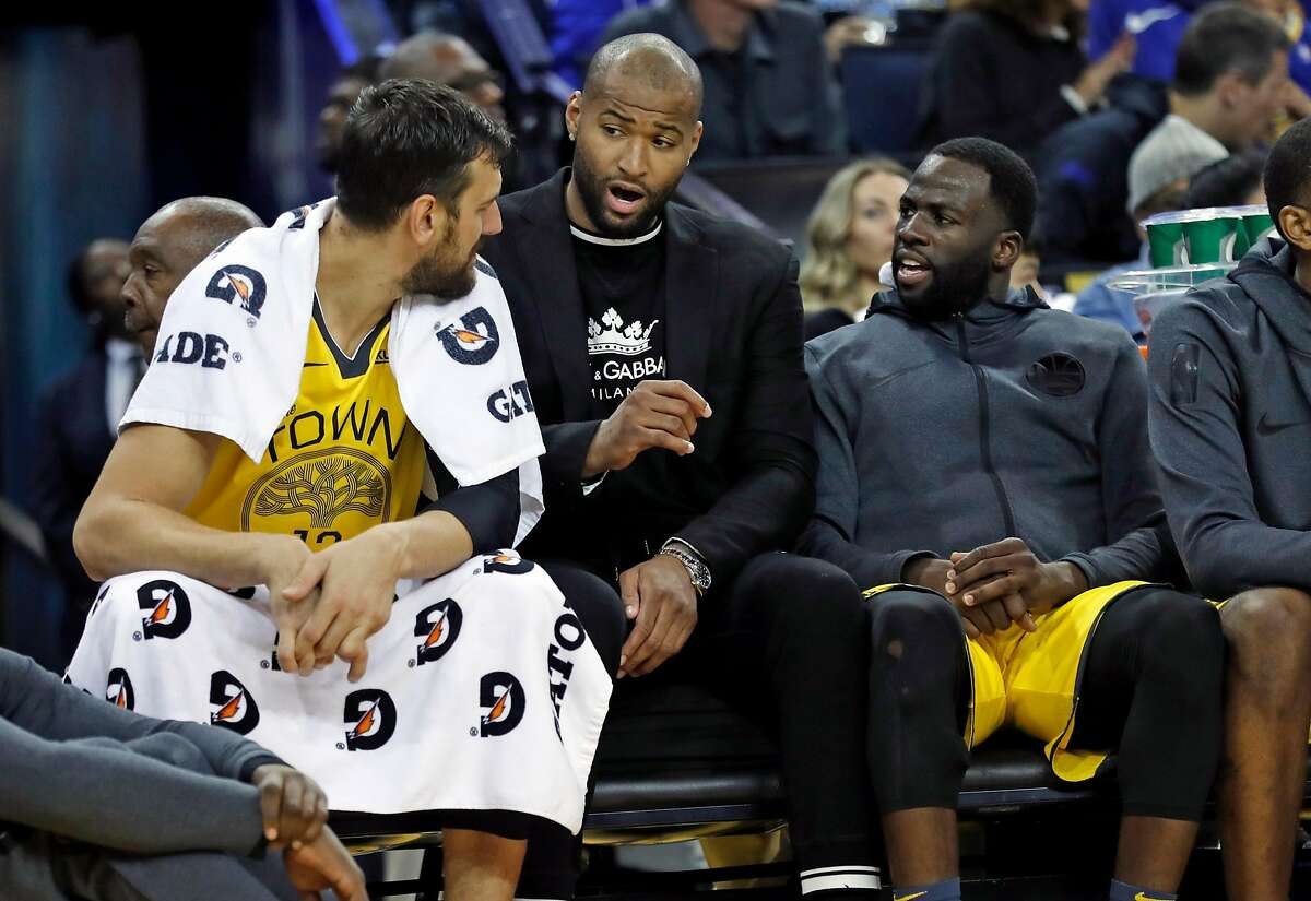 Golden State Warriors' DeMarcus Cousins talks with Andrew Bogut and Draymond Green on bench in 4th quarter of Warriors' 121-114 win over Detroit Pistons during NBA game at Oracle Arena in Oakland, Calif., on Sunday, March 24, 2019.