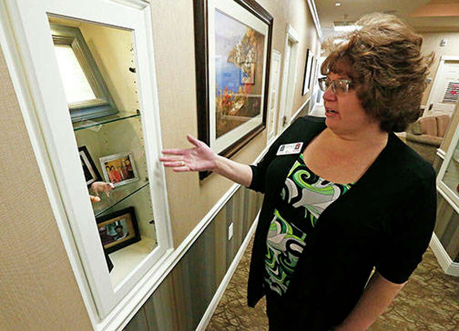 Arbor's director of nursing Kathie Palmer shows off a shadow box at Adams Pointe Senior Living in Quincy. The shadow boxes are for Alzheimer's residents and written history about each resident and mementos for the staff to help communicate with the residents. Photo: Jake Shane | Quincy Herald-Whig (AP)