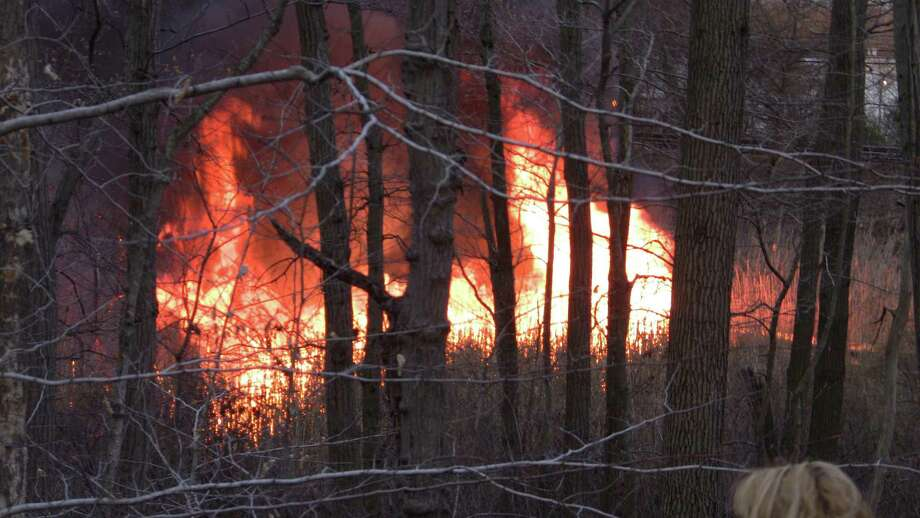 A major brush fire erupted shortly after 6pm Monday in Milford which caused Metro-North to halt train service in the area for part of the evening. It appears that most of the fire has been burning itself out but it is spread out over a very large area. Photo: Stephen Krauchick / Stephen Krauchick / Connecticut Post freelance