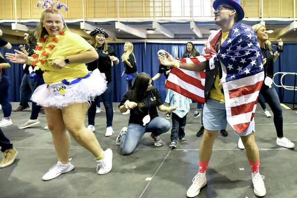 "Hamden, Connecticut - Saturday, March 23, 2019: Kyle Lopez, a Quinnipiac University senior and a ""morale dancer"", right, as he and other Quinnipiac University students dance for 10-hours Saturday in the school's Athletic Center in Hamden during QTHON, who are attempting to raise $323,000 for the Connecticut Children's Medical Center, a comprehensive pediatric hospital in Hartford."