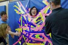 North Street School Principal, Jill Flood, hangs free after being taped to the gym wall during the Pennies for Patients fundraising campaign to benefit the Leukemia and Lymphoma Society. Friday, March 22, 2019
