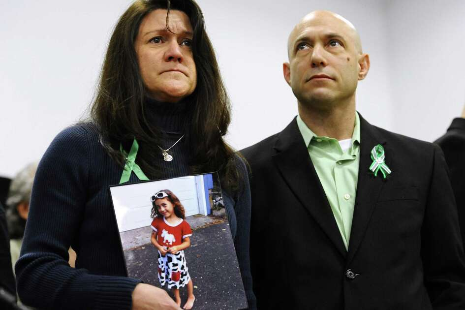 Jennifer Hensel, holding a portrait of her daughter, Avielle Rose Richman, stands with her husband Jeremy Richman at a news conference in Newtown in January 2013.