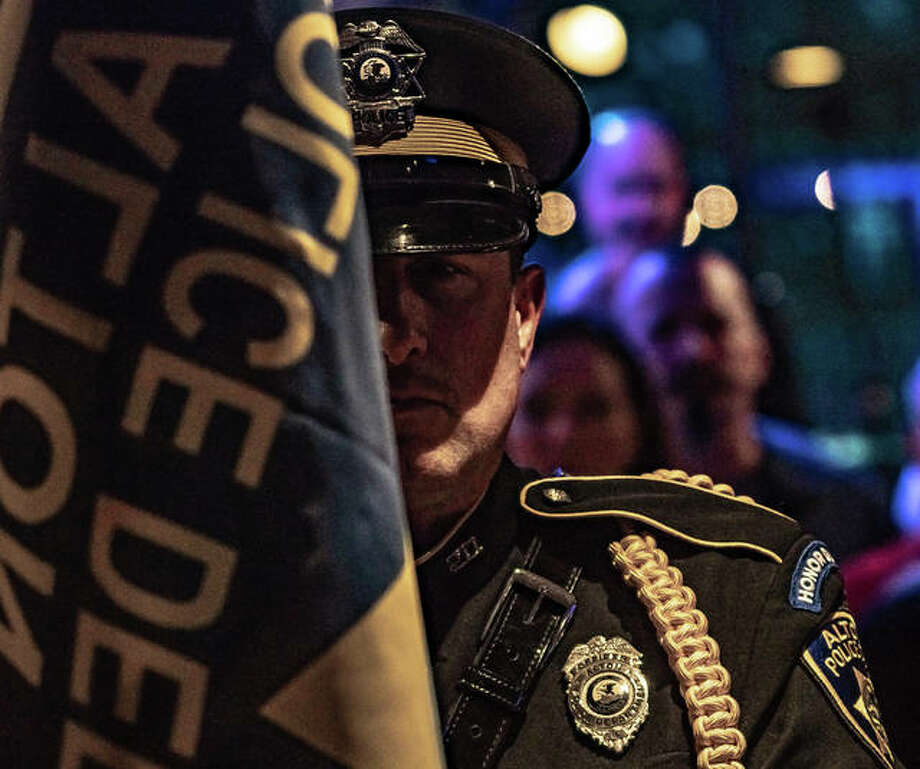 A member of the Alton Police Department Honor Guard stands at attention Friday with more than 100 police officers, firefighters and servicemen and women during the annual Mustache March 4PD event at Bluff City Bar and Grill. The event raised as much as $100,000. MM4PD board members pose for a photo Friday night. Photo: Nathan Woodside | The Intelligencer