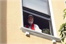 Ferlinghetti waves to singers from his kitchen window