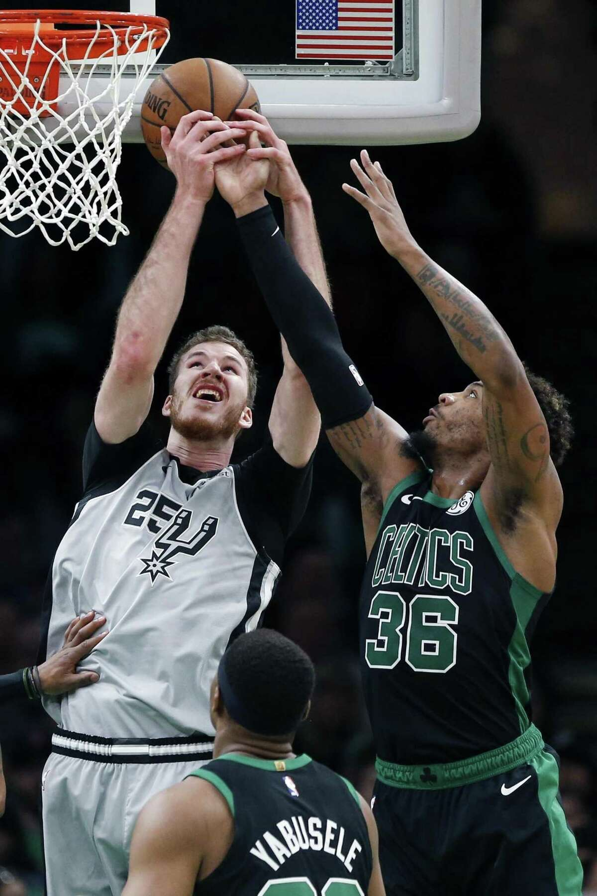 San Antonio Spurs' Jakob Poeltl (25) and Boston Celtics' Marcus Smart (36) vie for a rebound during the first half of an NBA basketball game in Boston, Sunday, March 24, 2019. (AP Photo/Michael Dwyer)