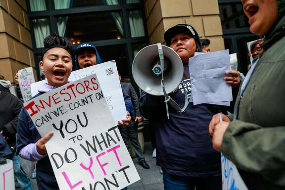 Malae Tulau, 15 (left) and others cheer during a protest against Lyft's paycuts as well as the company going public outside the Omni Hotel on Friday in San Francisco , California, on Monday, March 25, 2019. Drivers argue that their share has been cut significantly and that they are the backbone of the company.