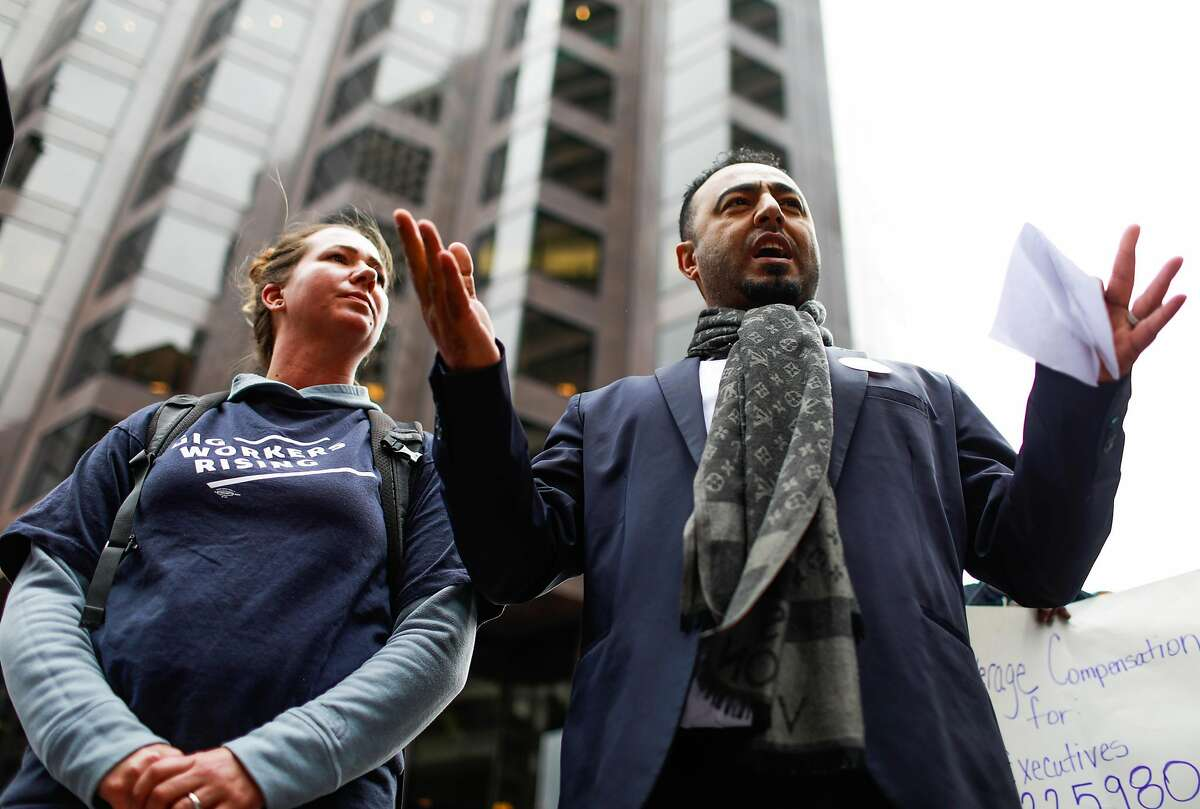 Omar Alkhameri (right) speaks to a group of Lyft drivers to kick off a protest against Lyft's paycuts as well as the company going public on Friday in San Francisco , California, on Monday, March 25, 2019. Drivers argue that their share has been cut significantly and that they are the backbone of the company.