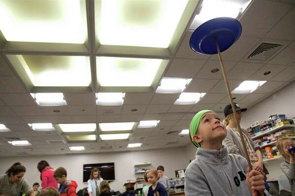 Juliet Olmstead, 8, of Fairfield, gets her plate moving at the circus arts demonstration at the Fairfield Woods Branch Library on Saturday, March 23, 2019, in Fairfield, Conn.