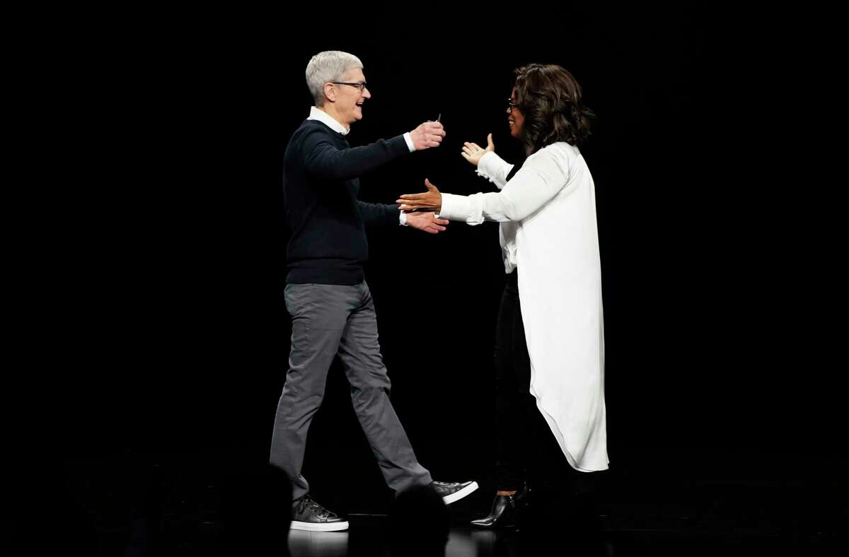 Apple CEO Tim Cook and Oprah Winfrey prepare to embrace at the Steve Jobs Theater during an event to announce new products Monday, March 25, 2019, in Cupertino, Calif.