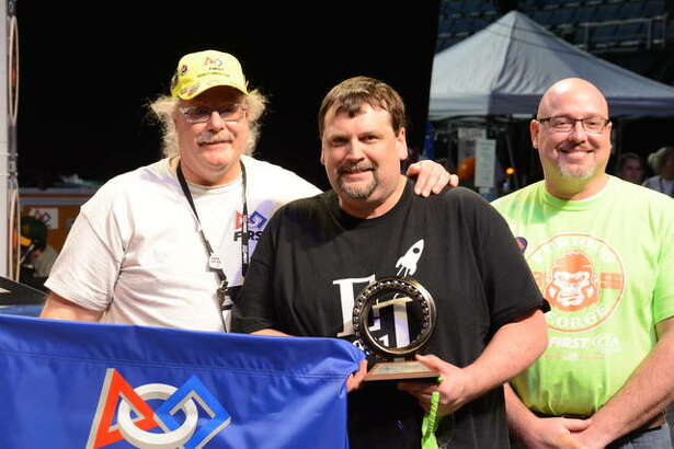 Rande Johnson, center, mentor to Team FRC 4931, Edwardsville Technologies, is a Woodie Flowers Finalist Award winner.