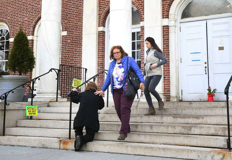 A woman takes a knee in prayer on the steps of Edmond Town Hall in Newtown, home of the Avielle Foundation, where Jeremy Richman, father of Sandy Hook victim Avielle Richman, was found dead from an apparent suicide Monday morning. Photo: Brian A. Pounds / Hearst Connecticut Media / Connecticut Post