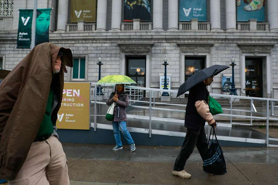 Martial York (right) walks on Larkin Street in the rain in San Francisco , California, on Monday, March 25, 2019. Photo: Gabrielle Lurie, The Chronicle