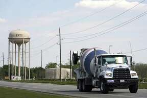 A concrete truck travels along U.S. 90 on March 20 near Katy's water tower.