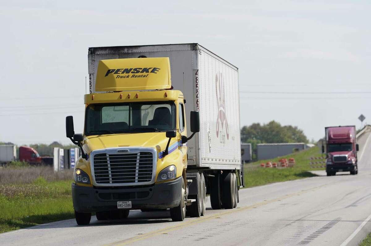 Two trucks travel along Pederson Road in Katy on March 20.