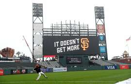 A San Francisco Giants' player plays long toss with the partially constructed new scoreboard in the background before Giants play the Oakland Athletics at Oracle Park in San Francisco, Calif., on Monday, March 25, 2019.