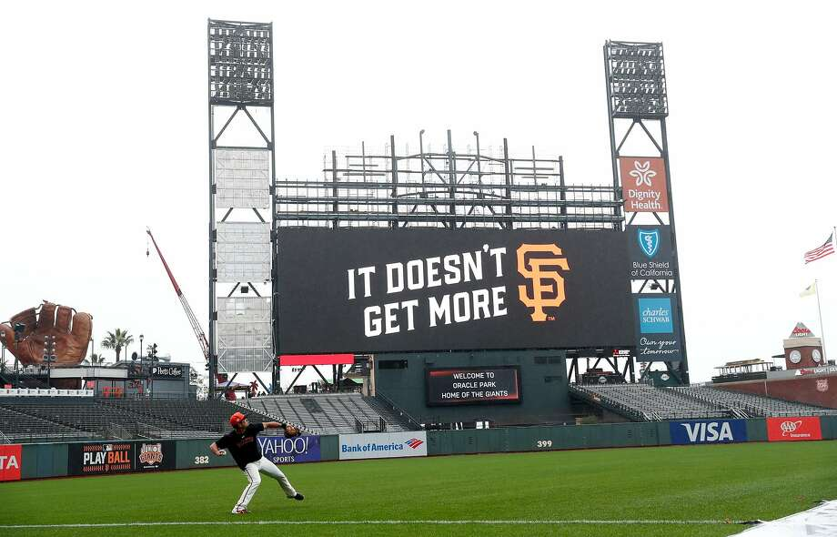 A San Francisco Giants' player plays long toss with the partially constructed new scoreboard in the background before Giants play the Oakland Athletics at Oracle Park in San Francisco, Calif., on Monday, March 25, 2019. Photo: Scott Strazzante / The Chronicle