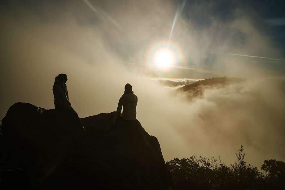 Ashley Meyers and Britt Williams Baker watch as the fog breaks through on the East Peak at Mount Tamalpais State Park in Mill Valley, Calif., on Wednesday, Dec. 19, 2018. Photo: Mason Trinca / Special To The Chronicle