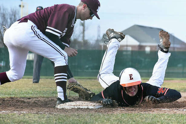 Edwardsville's Joe Copeland dives safely back into first base on a pickoff attempt by Moline during Monday's game at Tom Pile Field.