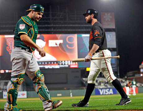 San Francisco Giants' Brandon Belt crosses paths with Oakland Athletics' Josh Phegley after striking out in 1st inning at Oracle Park in San Francisco, Calif., on Monday, March 25, 2019.