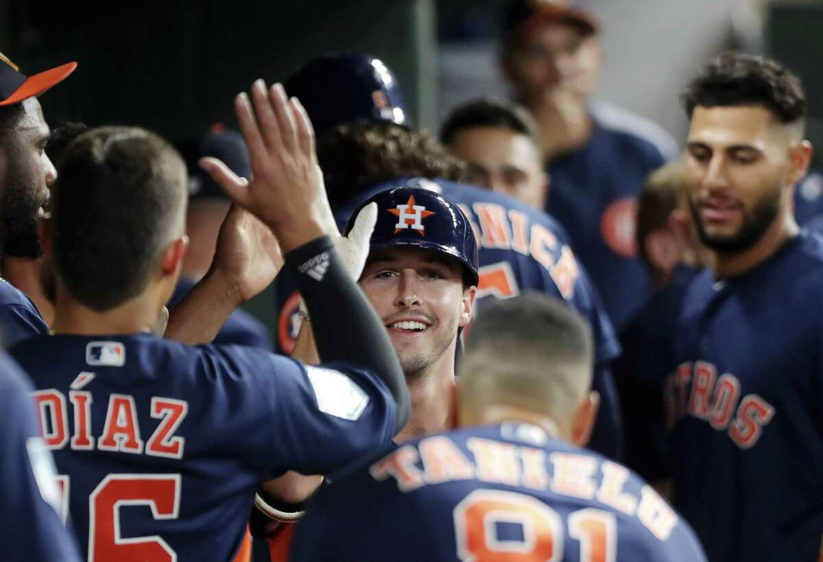 Houston Astros catcher Garrett Stubbs celebrates in the dugout after hitting a homerun during the seventh inning of a spring training game at Minute Maid Park on Monday, March 25, 2019, in Houston.